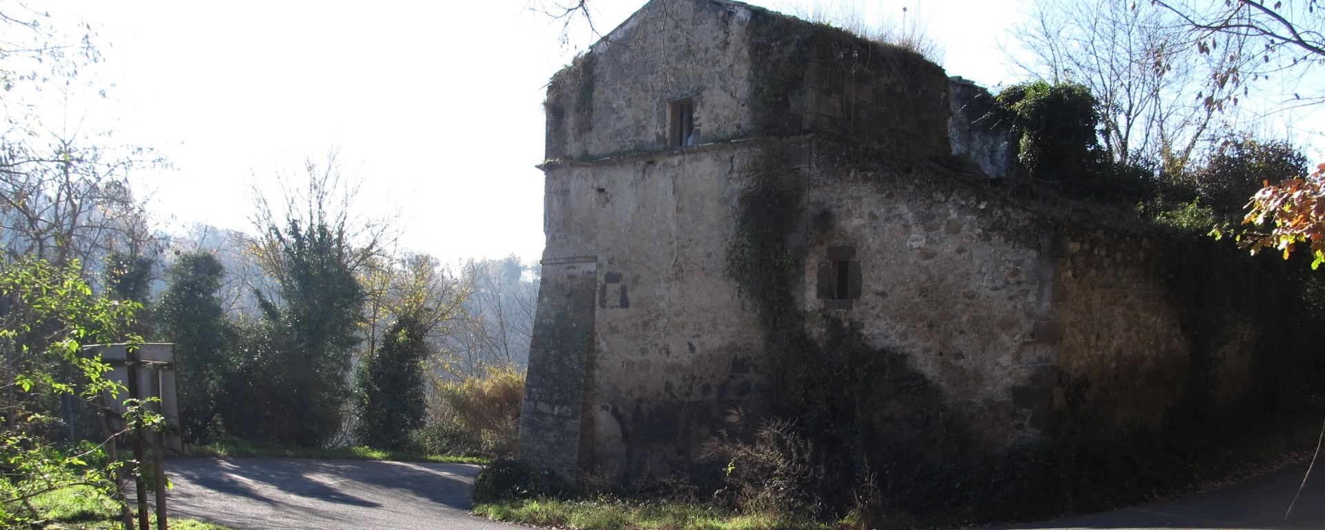 An Italian Provincial road forms a hairpin bend around an ancient and derelict farmhouse